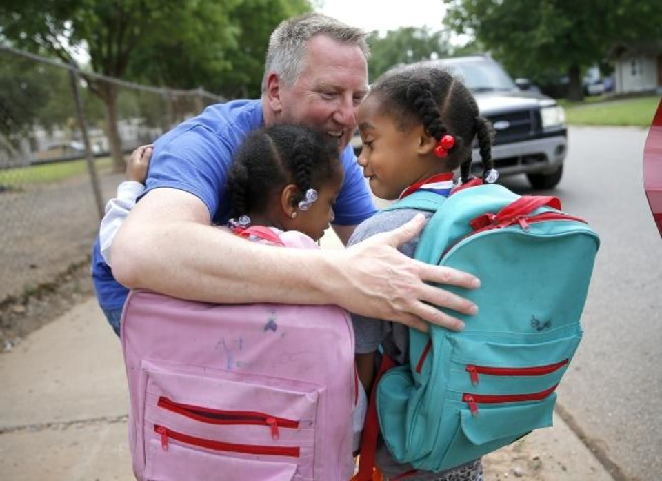 Photo -  Principal Mitch Ruzzoli hugs Melody McCauley and Lyric McCauley, 6,  goodbye as their parents pick them up on the last day of school at Horace Mann Elementary in Oklahoma City, Friday, May 24, 2019.  [Sarah Phipps/The Oklahoman]