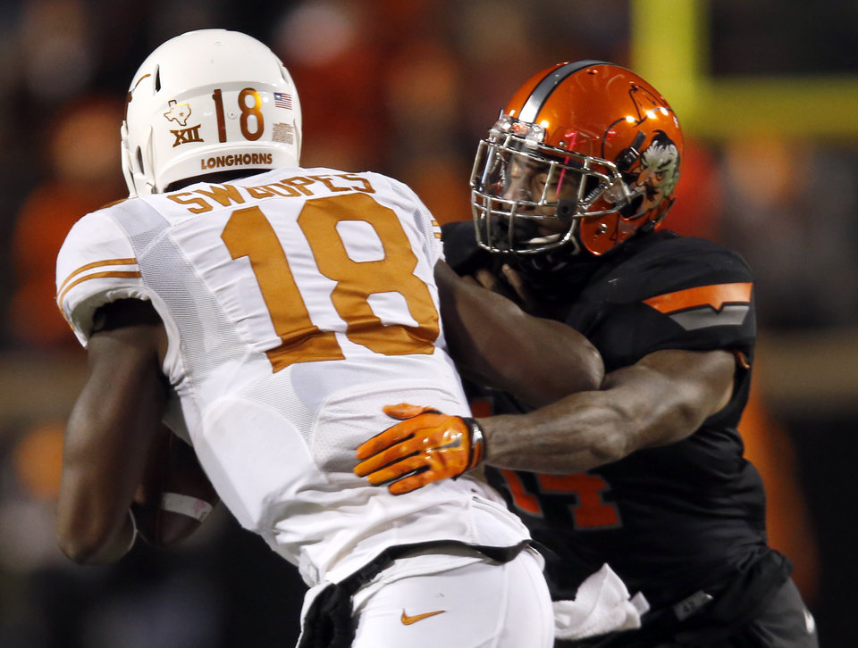 Photo - Oklahoma State's Josh Furman (14) sacks Texas Tyrone Swoopes (18) during the college football game between the Oklahoma State University Cowboys (OSU) the University of Texas Longhorns (UT) at Boone Pickens Staduim in Stillwater, Okla. on Saturday, Nov. 15, 2014.  Photo by Sarah Phipps, The Oklahoman