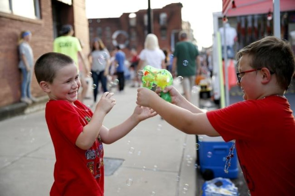 Photo -  Parker Kesler, 8, at right, and his cousin, Aart Locke, 5, play with bubbles during Red Brick Nights. [BRYAN TERRY/THE OKLAHOMAN]