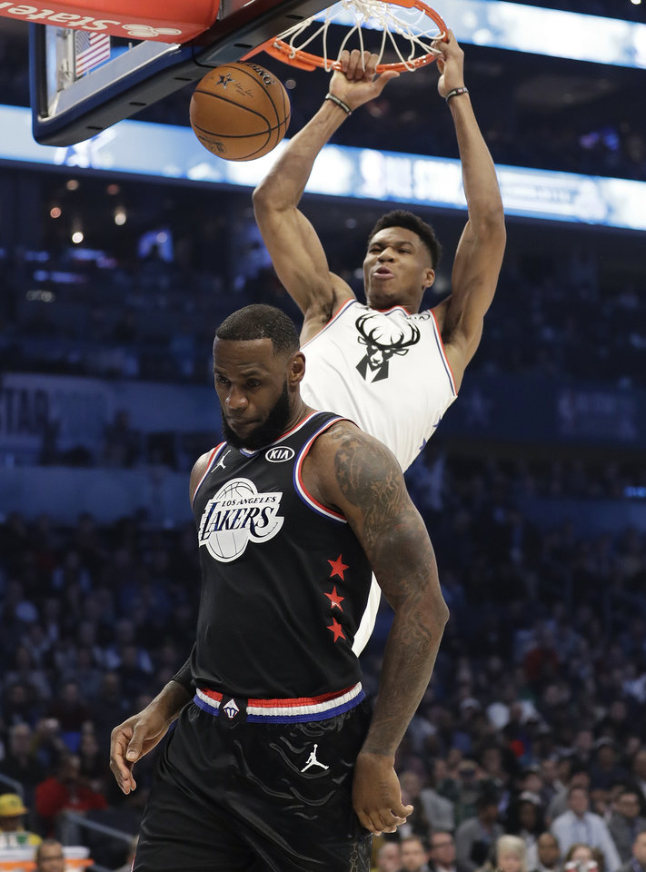 Photo - Team Giannis' Giannis Antetokounmpo, of the Milwaukee Bucks, dunks the ball against Team LeBron's LeBron James, of the Cleveland Cavaliers, during the first half of an NBA All-Star basketball game, Sunday, Feb. 17, 2019, in Charlotte, N.C. (AP Photo/Chuck Burton)