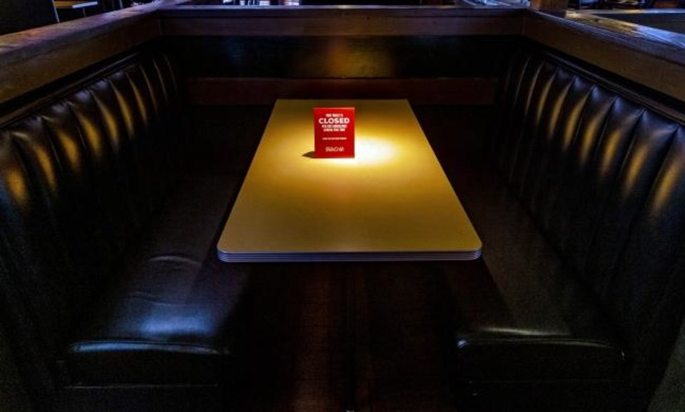 Photo -  Signs mark closed seating areas that follow the CDC's social distancing guidelines at a Rib Crib restaurant in April. [Chris Landsberger/The Oklahoman]