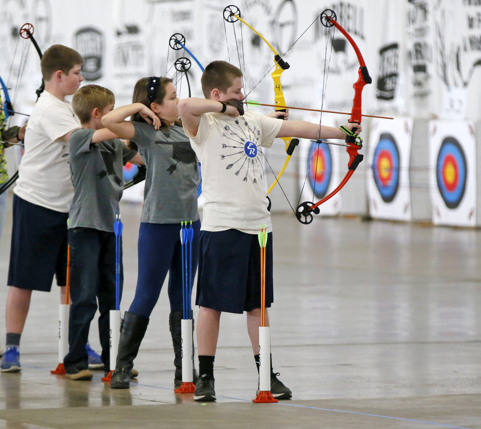 Photo -  Students compete in the Oklahoma National Archery in the Schools state championships at State Fair Park in February. [PHOTO BY NATE BILLINGS, THE OKLAHOMAN]