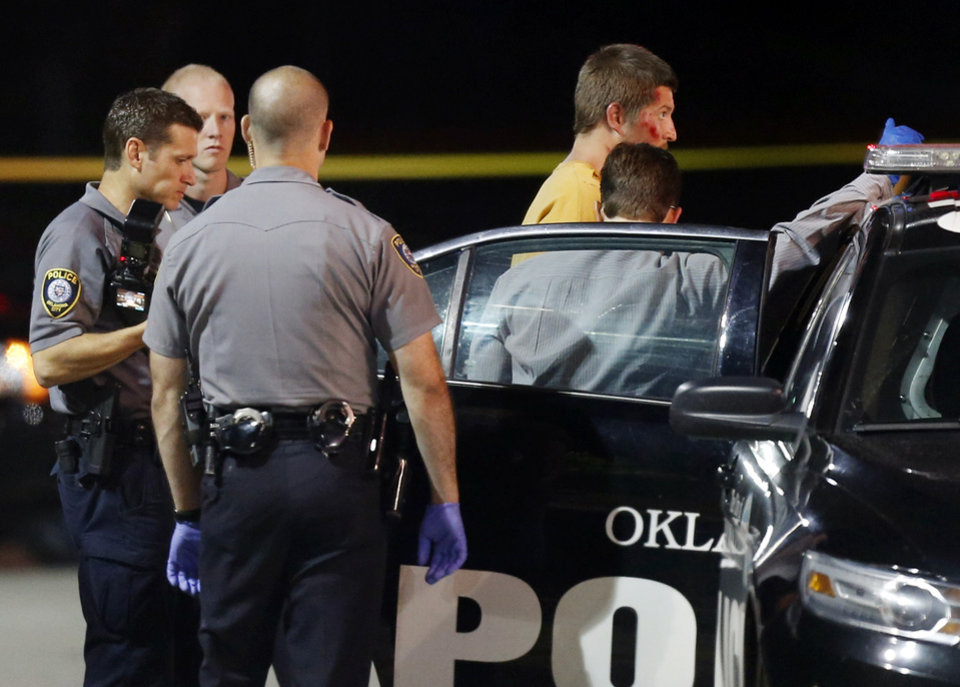 Photo - Oklahoma City police take photos of Christian Costello, son of Labor Commissioner Mark Costello, before returning him to the back of a police car at a Braum's restaurant on May and NW 112th St. where Mark Costello was fatally stabbed, Sunday, Aug. 23, 2015.  Photo by Nate Billings, The Oklahoman