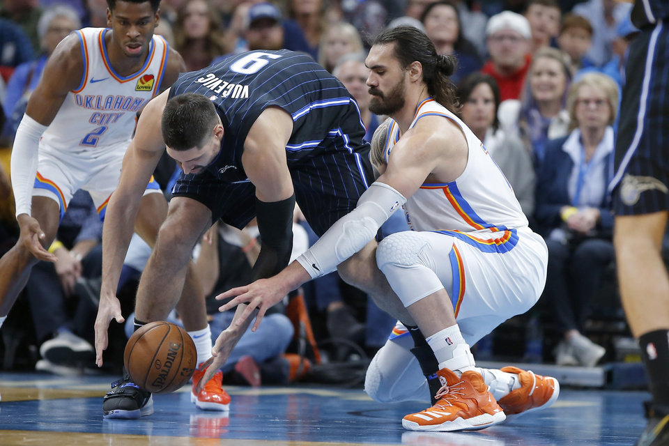Photo - Oklahoma City's Steven Adams (12) goes for the ball beside Orlando's Nikola Vucevic (9) during an NBA basketball game between the Oklahoma City Thunder and the Orlando Magic at Chesapeake Energy Arena in Oklahoma City, Tuesday, Nov. 5, 2019. Oklahoma City won 102-94. [Bryan Terry/The Oklahoman]