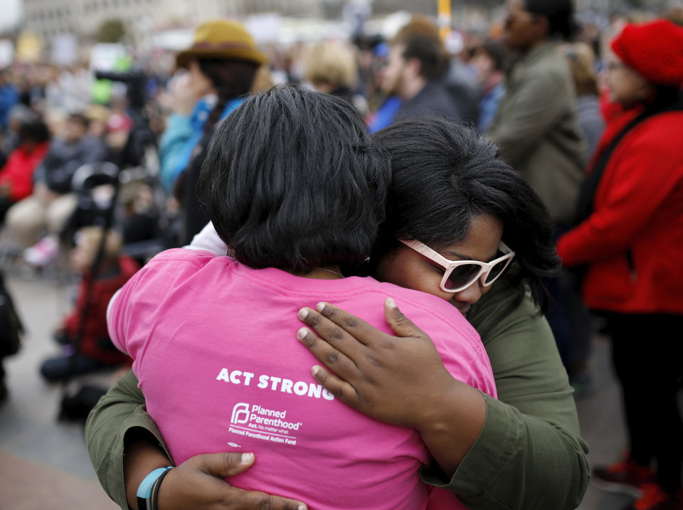 Photo - Brondalyn Coleman, wearing sunglasses, embraces Tamya Cox a few feet from the stage after Cox finished her address to the crowd. Cox is with Planned Parenthood Great Plains in Oklahoma. A crowd estimated by organizers to be as many as 7,000 people came to the state Capitol in Oklahoma City Saturday, Jan. 21, 2017, to rally, using their voices and signs to express displeasure with the nation's new administration as part of a larger network of marches taking place across the country following Donald Trump's inauguration.   The Women's March on Oklahoma included a walk along Lincoln Blvd., with the Capitol as a backdrop, and a rally on the Capitol's south plaza that featured nearly a dozen speakers.  Photo by Jim Beckel, The Oklahoman