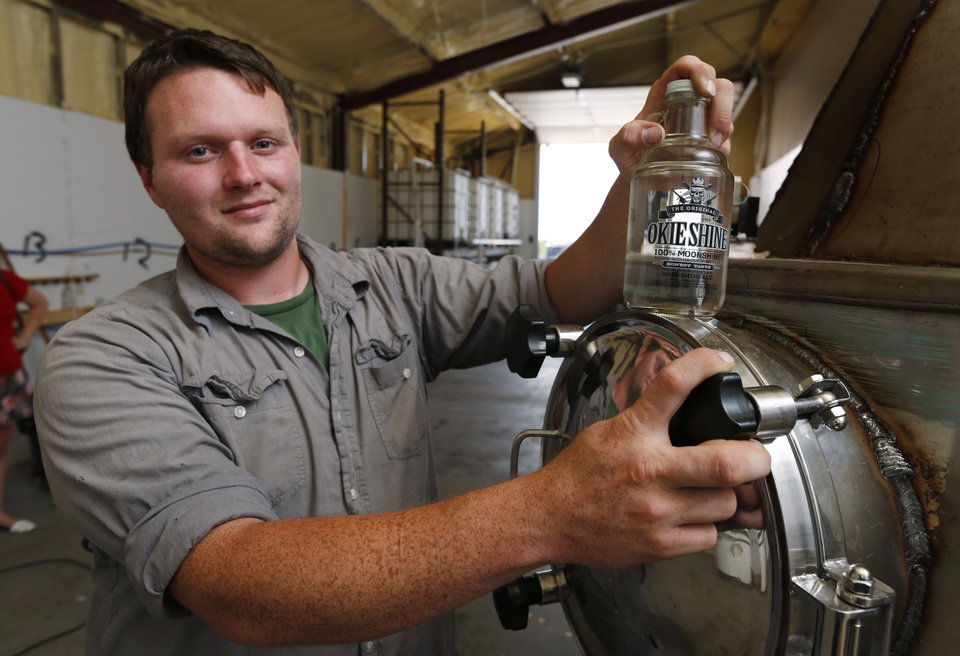 Photo -  Ricky Sowers displays a bottle of moonshine produced at his Okie Shine distillery on Wednesday in Tuttle. Sowers says Okie Shine is the first legal distiller of moonshine in the state. [Photo by Steve Sisney, The Oklahoman]