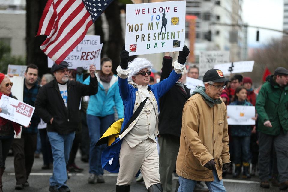 Photo - People participate in a protest Monday, Feb. 20, 2017, in Portland, Ore. Thousands of demonstrators turned out Monday across the U.S. to challenge President Donald Trump in a Presidents Day protest dubbed Not My President's Day. (Dave Killen/The Oregonian via AP)