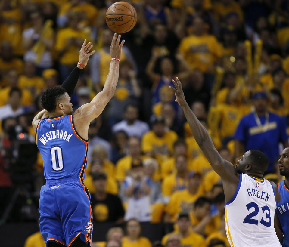 Photo - Oklahoma City's Russell Westbrook (0) shoots a 3-pointer over Golden State's Draymond Green (23) during Game 5 of the Western Conference finals in the NBA playoffs between the Oklahoma City Thunder and the Golden State Warriors at Oracle Arena in Oakland, Calif., Thursday, May 26, 2016. Photo by Nate Billings, The Oklahoman