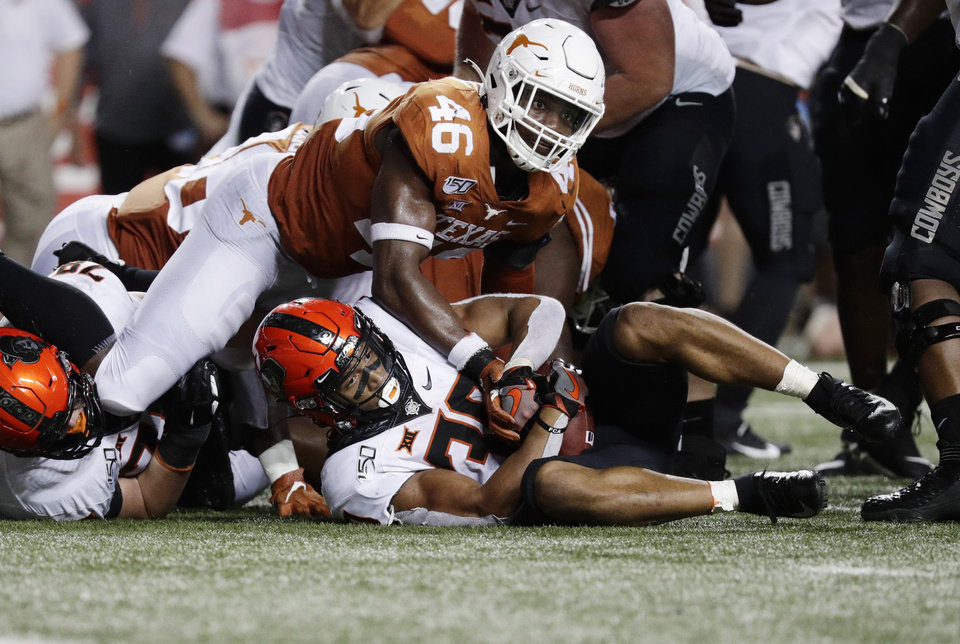 Photo - Oklahoma State running back Chuba Hubbard (30) is stopped short of a first down by Texas linebacker Joseph Ossai (46) on fourth down near the goal line during the second half of an NCAA college football game Saturday, Sept. 21, 2019, in Austin, Texas. (AP Photo/Eric Gay)