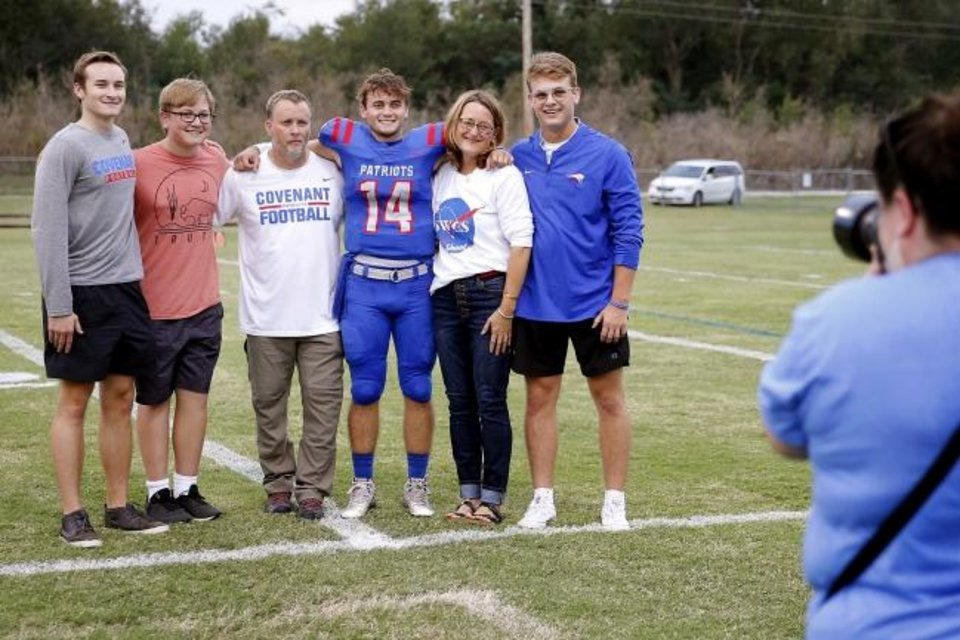 Photo -  It has been a year since Southwest Covenant football Peter Webb died after suffering a head injury during a game. His family, from left, brother Jack, brother Hank, father Jim, brother Ben, mother Stacy and brother Sam, seen here before the homecoming game last season, continue to grieve. [BRYAN TERRY/THE OKLAHOMAN]
