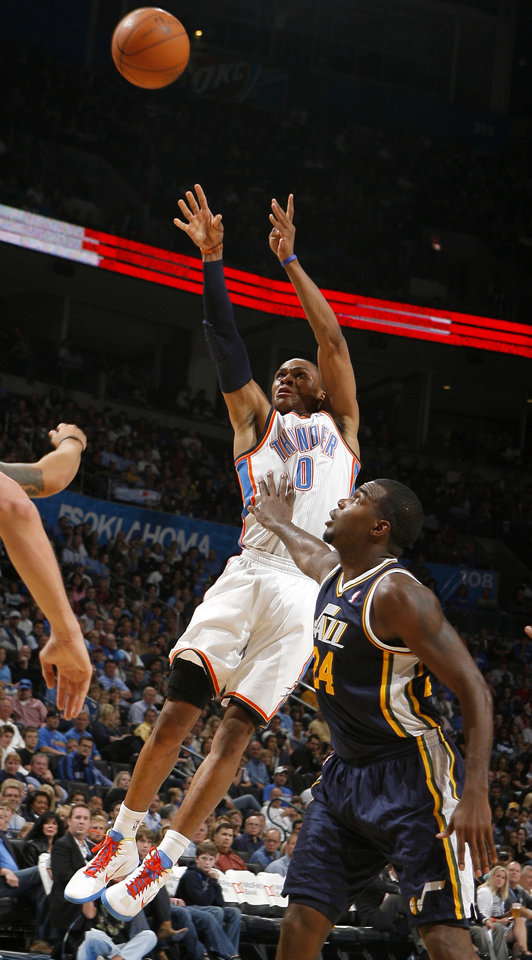 Photo - Oklahoma City's Russell Westbrook shoots as Utah's Paul Millsap defends during the NBA basketball game between the Oklahoma City Thunder and Utah Jazz in the Oklahoma City Arena on Sunday, Oct. 31, 2010. Photo by Sarah Phipps, The Oklahoman