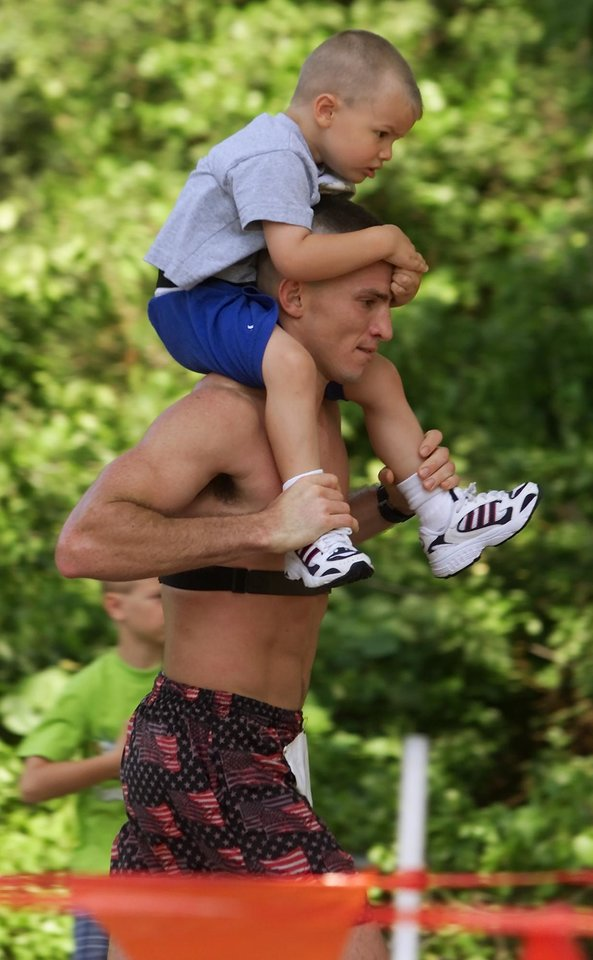 Photo - Andy Payne Memorial Marathon (Footrace) at Lake Overholser. Marathon race. Marathon runner Brian Woodall runs the last part of the race with his son Mason Colby Woodall, 3, on his shoulder. The Woodalls live near Edmond.
