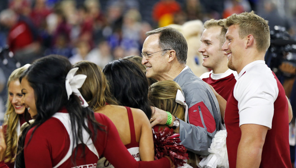 Photo - Oklahoma coach Lon Kruger poses for a photo with members of the OU spirit quads during practice on Final Four Friday before the national semifinal between the Oklahoma Sooners and the Villanova Wildcats in the NCAA Men's Basketball Championship at NRG Stadium in Houston, Friday, April 1, 2016. OU will play Villanova in the Final Four on Saturday. Photo by Nate Billings, The Oklahoman