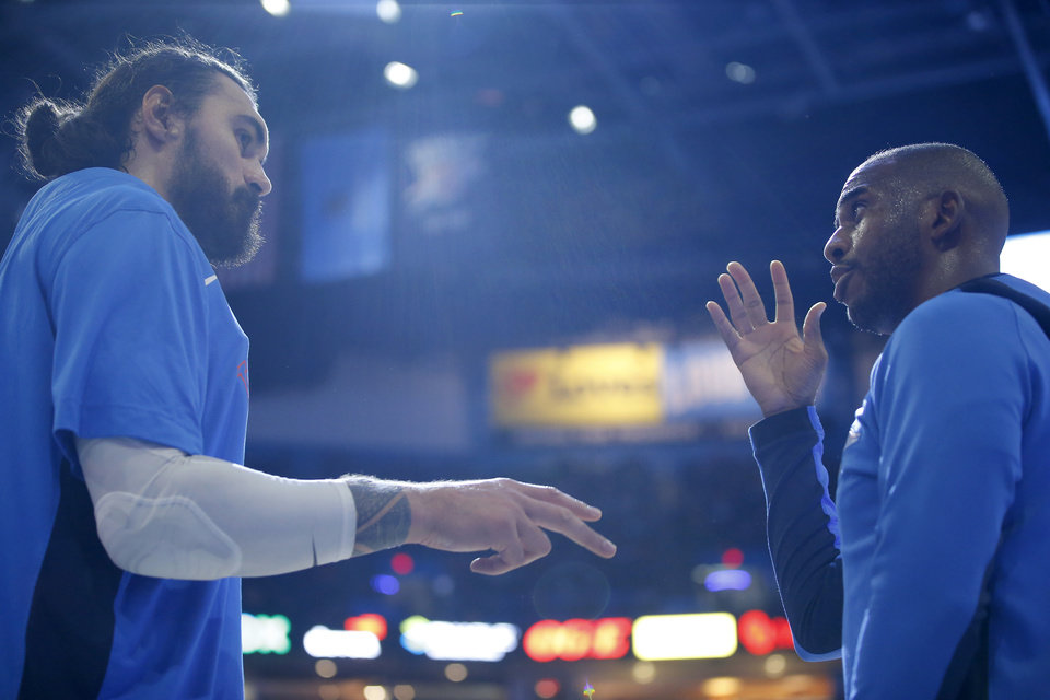 Photo - Oklahoma City's Steven Adams talks with Chris Paul during a timeout in an NBA basketball game between the Oklahoma City Thunder and the Orlando Magic at Chesapeake Energy Arena in Oklahoma City, Tuesday, Nov. 5, 2019. Oklahoma City won 102-94. [Bryan Terry/The Oklahoman]