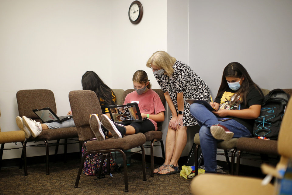 Photo - Children study inside Henderson Hills Baptist Church in Edmond, Okla., Wednesday, Aug. 26, 2020. The church has begun offering Edmond school students a place to go on Wednesdays to get homework help, use the free wi-fi for virtual learning, free lunch and other activities. [Bryan Terry/The Oklahoman]