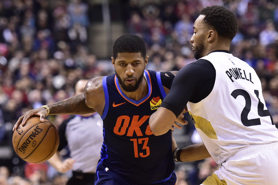 Photo - Oklahoma City Thunder forward Paul George (13) dribbles past Toronto Raptors forward Norman Powell (24) during second-half NBA basketball game action in Toronto, Friday, March 22, 2019. (Frank Gunn/The Canadian Press via AP)