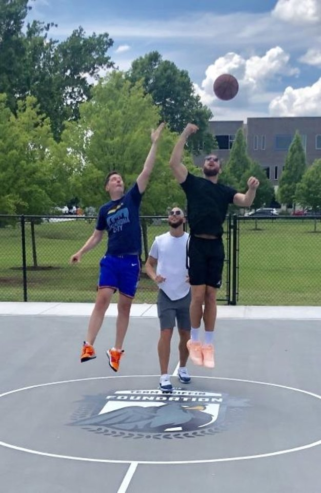 Photo -  Oklahoma City Mayor David Holt, left, squares off Sunday against NBA star Blake Griffin as Griffin's brother Taylor tosses a jump ball. The tipoff, won by Blake,, kicked off the opening of downtown's newest park, Together Square. [PROVIDED]