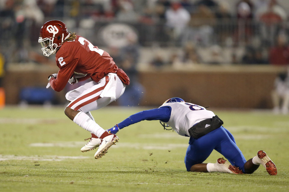 Photo - Oklahoma's CeeDee Lamb (2) gets past Kansas' Shakial Taylor (8) during a college football game between the University of Oklahoma Sooners (OU) and the Kansas Jayhawks (KU) at Gaylord Family-Oklahoma Memorial Stadium in Norman, Okla., Saturday, Nov. 17, 2018. Photo by Bryan Terry, The Oklahoman