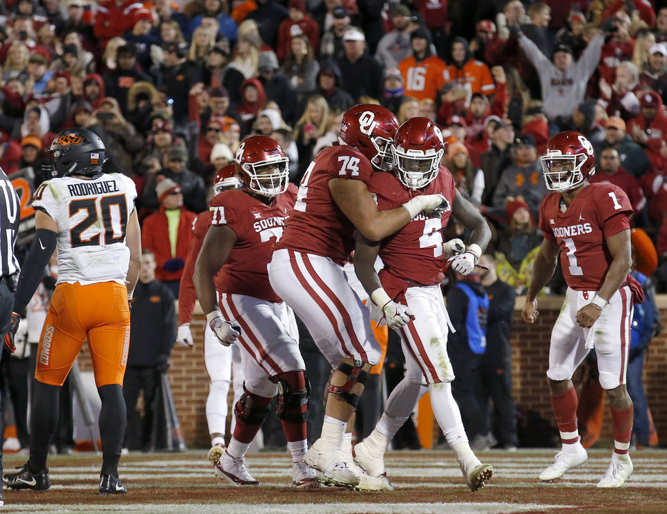 Photo - Oklahoma celebrates a Oklahoma's Trey Sermon (4) touchdown  in the fourth quarter during a Bedlam college football game between the University of Oklahoma Sooners (OU) and the Oklahoma State University Cowboys (OSU) at Gaylord Family-Oklahoma Memorial Stadium in Norman, Okla., Nov. 10, 2018.  Photo by Sarah Phipps, The Oklahoman