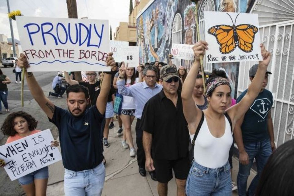 Photo -  People march in silence Sunday in El Paso, Texas, holding sunflowers and signs to honor the victims of the mass shooting that occurred in Walmart on Saturday. [Lola Gomez/Austin American-Statesman]