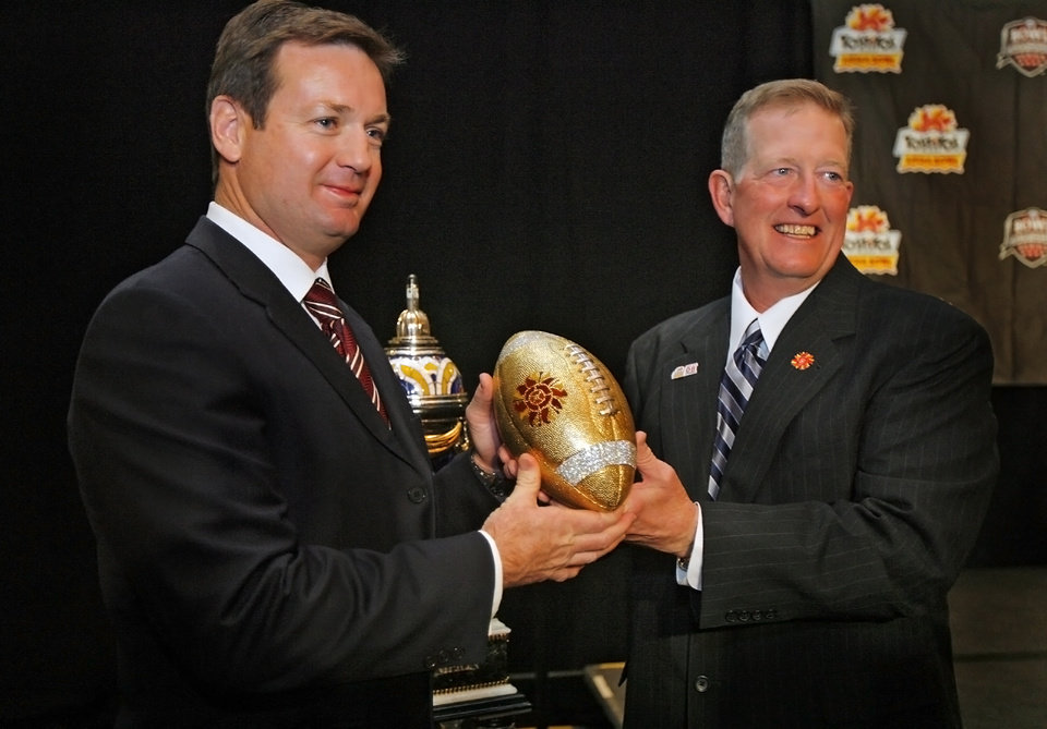 Photo - OU, COLLEGE FOOTBALL: The University of Oklahoma head coach Bob Stoops and West Virginia University interim head coach Bill Stewart, from left, pose for a photo with the gold football from the Fiesta Bowl trophy during the Fiesta Bowl coaches press conference on Tuesday, Jan. 1, 2008, in Scottsdale, Ariz. The Sooners will play the West Virginia Mountaineers on Wednesday in the Fiesta Bowl.  BY CHRIS LANDSBERGER, THE OKLAHOMAN ORG XMIT: KOD