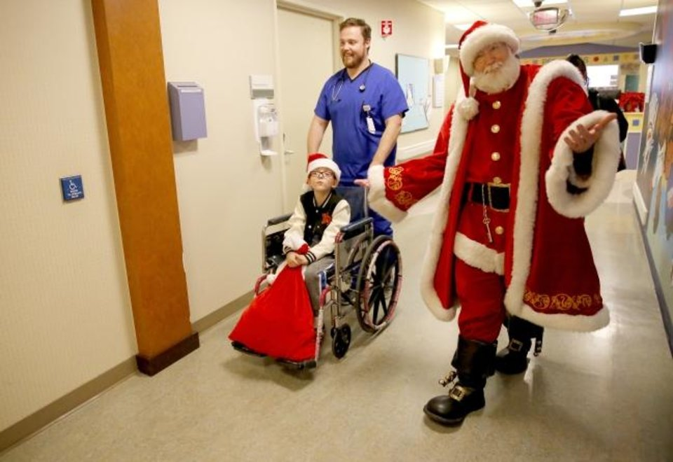 Photo -  Santa Claus accompanies Tyler Slife, R.N., and Logan Harrison, 7, as Logan is discharged from the hospital on Christmas Eve.   [Sarah Phipps/The Oklahoman]