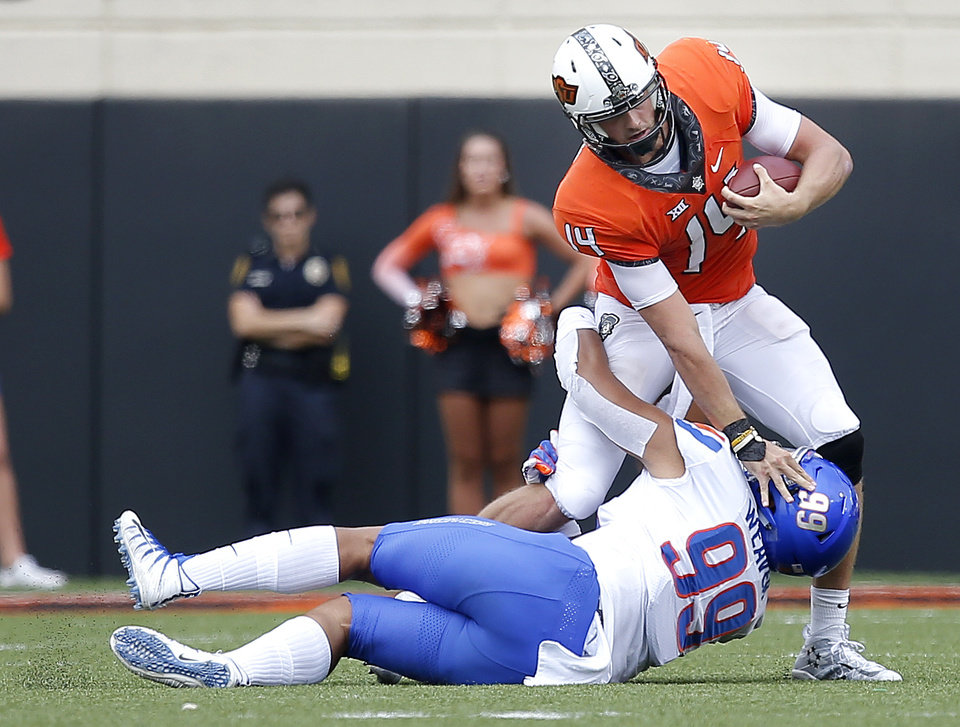Photo - Oklahoma State's Taylor Cornelius (14) tries to get by Boise State's Curtis Weaver (99) in the third quarter during a college football game between the Oklahoma State Cowboys (OSU) and the Boise State Broncos at Boone Pickens Stadium in Stillwater, Okla., Saturday, Sept. 15, 2018. OSU won 44-21. Photo by Sarah Phipps, The Oklahoman