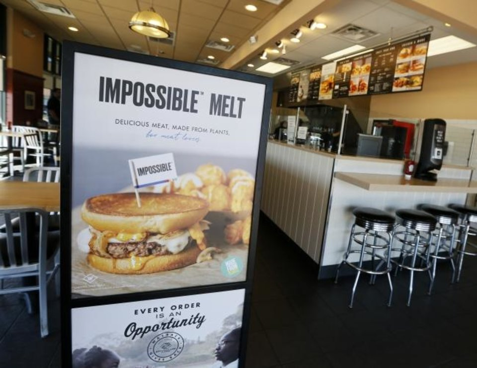 Photo -  A sign for the plant-based Impossible Melt is displayed at Wayback Burgers in Edmond.   [Nate Billings/The Oklahoman]