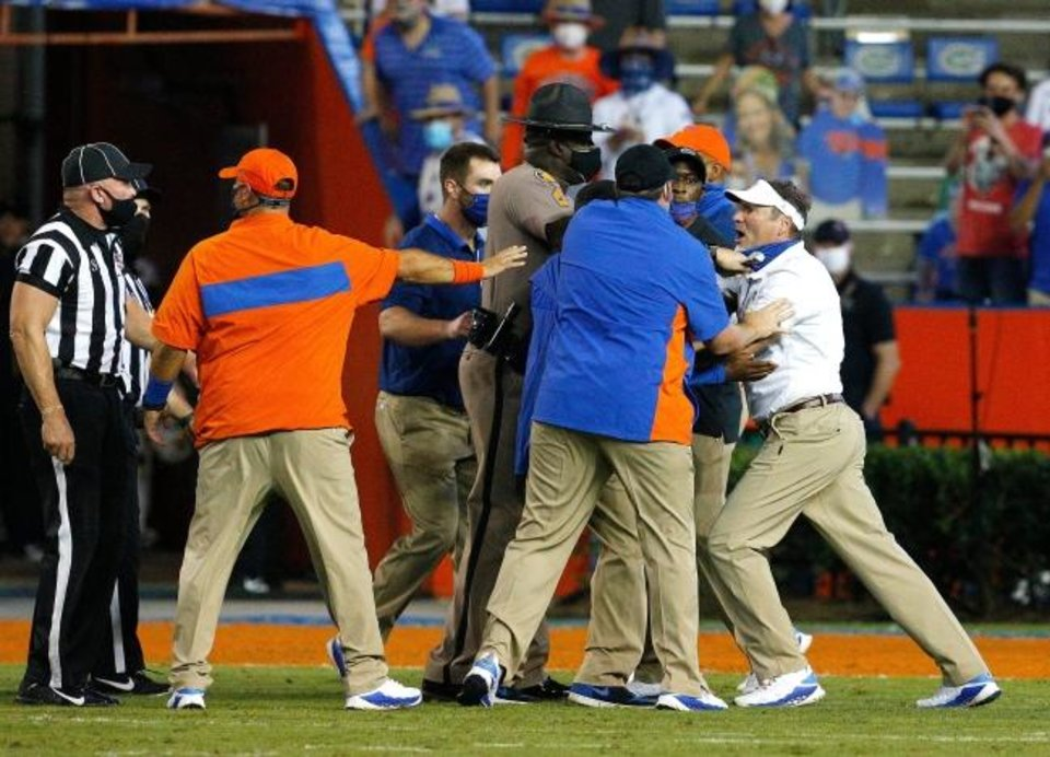Photo -  Florida head coach Dan Mullen, far right, is held back by coaches and law enforcement after a fight broke out at the end of the first half against the Missouri on Oct. 31. [Brad McClenny/The Gainesville Sun]