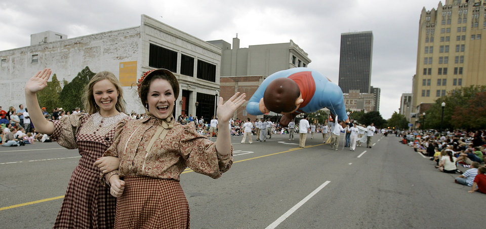 Photo - Angela Weichbrodt 16 of OKC and Leah Coleman 15 of Edmond walk in  front of the Will Rogers Balloon along E.K. Gaylord Blvd. in the Oklahoma Centennial Parade Saturday, Oct. 14, 2007 BY JACONNA AGUIRRE/THE OKLAHOMAN.