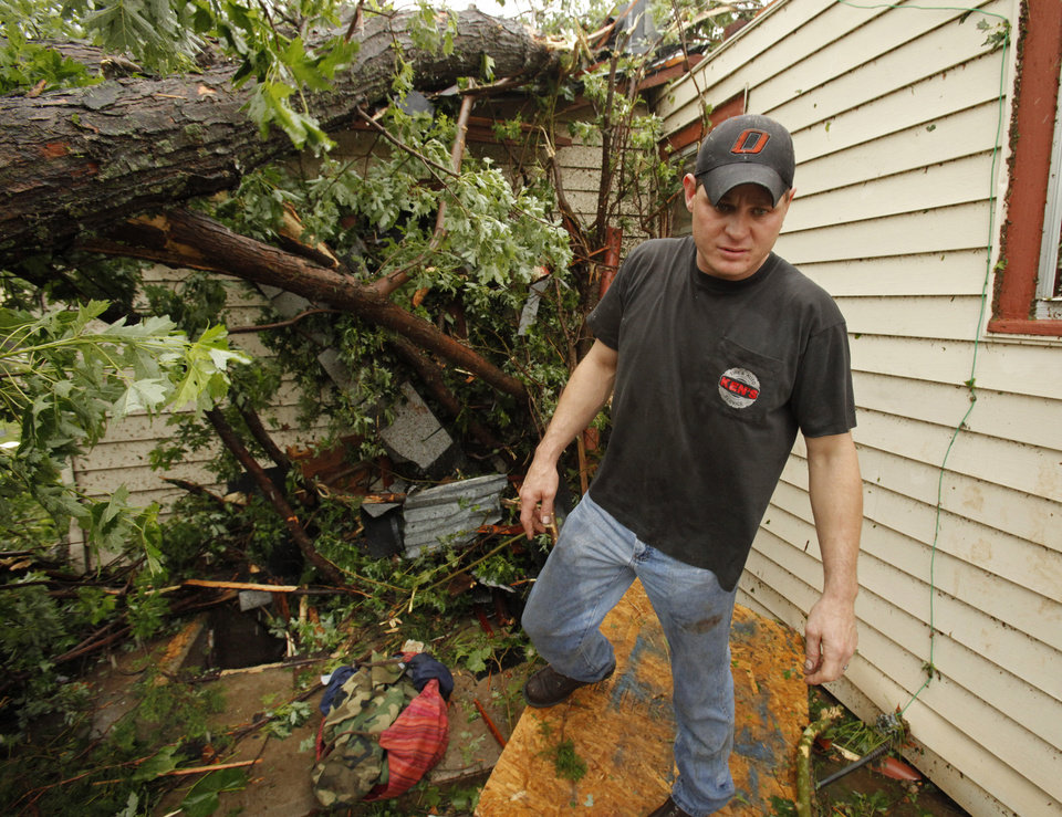 Photo - Bryan Stout walks past the tree that temporarily blocked his family's exit from the storm shelter where they rode out a tornado-spawning storm on Tuesday, May 24, 2011, in Newcastle, Okla. Photo by Steve Sisney, The Oklahoman