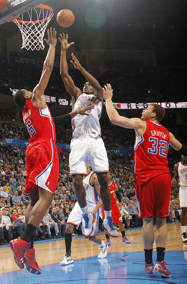 Photo - Oklahoma City Thunder power forward Serge Ibaka (9) puts up a shot over Los Angeles Clippers center DeAndre Jordan (6) and Los Angeles Clippers power forward Blake Griffin (32) during the NBA basketball game between the Oklahoma City Thunder and the Los Angeles Clippers at Chesapeake Energy Arena on Wednesday, March 21, 2012 in Oklahoma City, Okla.  Photo by Chris Landsberger, The Oklahoman