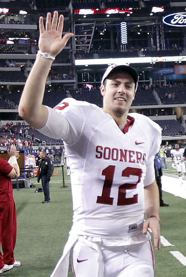Photo - Oklahoma's Landry Jones (12) waves to fans as he runs off the field after the Sooners' 23-20 win over Nebraska during the Big 12 football championship game between the University of Oklahoma Sooners (OU) and the University of Nebraska Cornhuskers (NU) at Cowboys Stadium on Saturday, Dec. 4, 2010, in Arlington, Texas.  Photo by Chris Landsberger, The Oklahoman