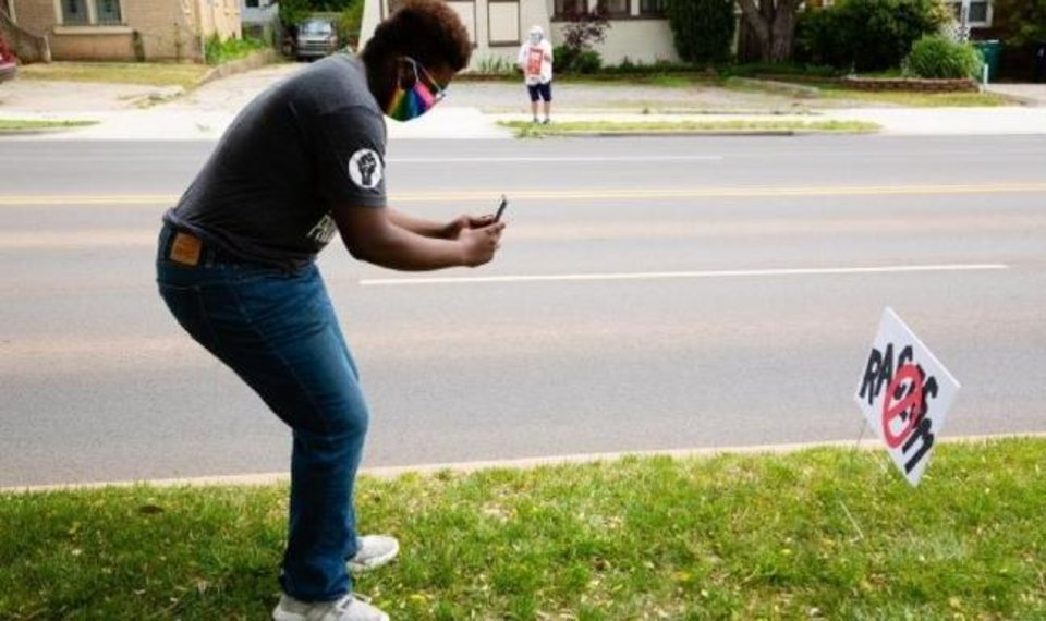 Photo -  Jay Williams uses his phone to take a picture of an anti-racism sign on NW 23 outside Oklahoma City University. The sign was posted in response to a racist and anti-semitic incident that occurred during OCU's virtual commencement. [Joshua Robinson/OCU]