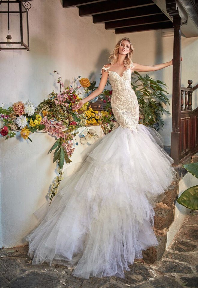 "Photo - ""Zenia,"" a French lace mermaid fit-and-flare dramatic gown with a low illusion back embroidered with large appliques and a two-toned handkerchief skirt for a signature Galia Lahav-style gown."