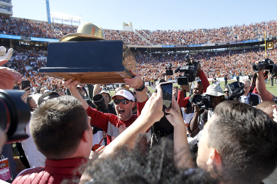 Photo - Oklaoma coach Lincoln Riley hands the Golden Hat to his team after the Red River Showdown college football game between the University of Oklahoma Sooners (OU) and the Texas Longhorns (UT) at Cotton Bowl Stadium in Dallas, Saturday, Oct. 12, 2019. Oklahoma won 34-27. [Bryan Terry/The Oklahoman]