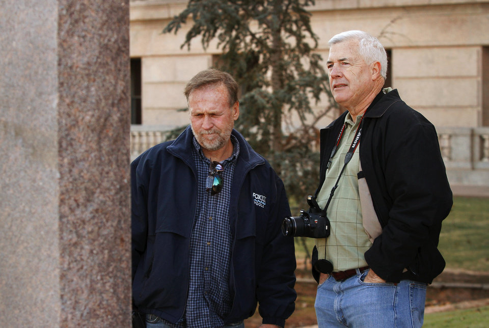 Photo - Two men, including State Rep. Mike Reynolds, right, look at the face of the monument after a six-foot tall granite replica of the Ten Commandments  was erected on the north side of the state Capitol grounds Thursday morning, Nov. 15, 2012.  Photo by Jim Beckel, The Oklahoman