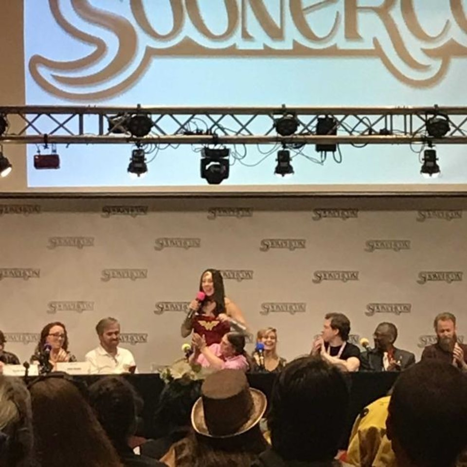 Photo -  Norman Mayor-Elect Breea Clark, dressed as Wonder Woman, speaks at SoonerCon, surrounded by the show's featured guests.  [Matthew Price]