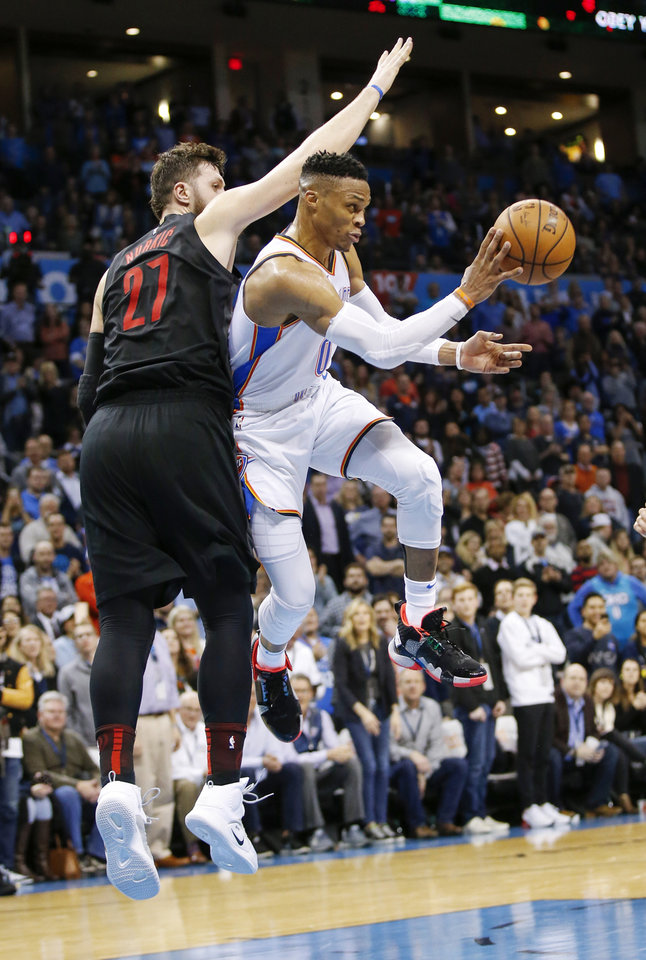 Photo - Oklahoma City's Russell Westbrook (0) passes next to Portland's Jusuf Nurkic (27) in the fourth quarter during an NBA basketball game between the Portland Trail Blazers and the Oklahoma City Thunder at Chesapeake Energy Arena in Oklahoma City, Monday, Feb. 11, 2019. Oklahoma City won 120-111. Photo by Nate Billings, The Oklahoman