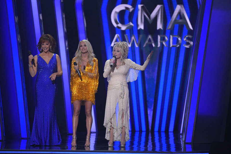 Photo - Hosts Reba McEntire, from left, Carrie Underwood and Dolly Parton appear at the 53rd annual CMA Awards at Bridgestone Arena, Wednesday, Nov. 13, 2019, in Nashville, Tenn. (AP Photo/Mark J. Terrill)