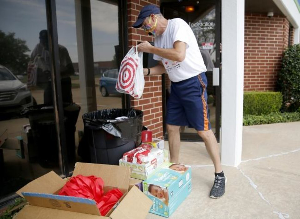 Photo -  Jeff Gross, Camp Chaverim Leadership In Training assistant director,  collects baby items outside the Jewish Federation of Greater Oklahoma City during the camp's drive-thru baby shower. [Bryan Terry/The Oklahoman]