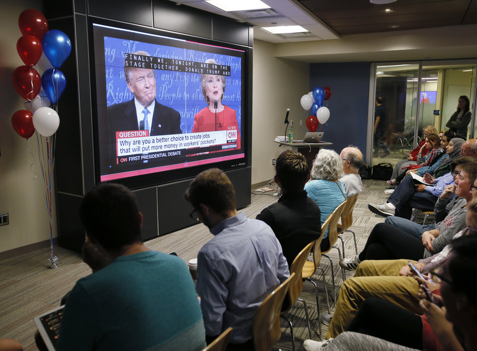 Photo - People watch the first presidential debate between Hillary Clinton and Donald Trump during a watch party on the lower level of the Bizzell Memorial Library on the campus of the University of Oklahoma in Norman, Okla., Monday, Sept. 26, 2016. Photo by Nate Billings, The Oklahoman