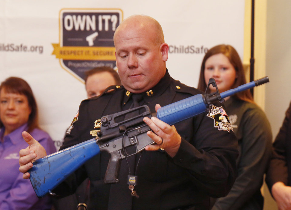 Photo -  Oklahoma County sheriff's Capt. Jim Anderson demonstrates firearm cable locks Wednesday during a Project Childsafe Communities announcement. [Photo by Paul Hellstern, The Oklahoman]