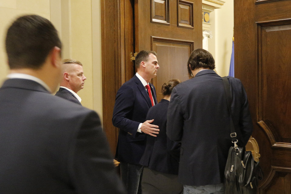Photo - Gov. Kevin Stitt returns to his office after a the Oklahoma government officials had a press conference to discuss the state's response to the Covid-19 Thursday, March 12, 2020.  [Photo by Doug Hoke/The Oklahoman]