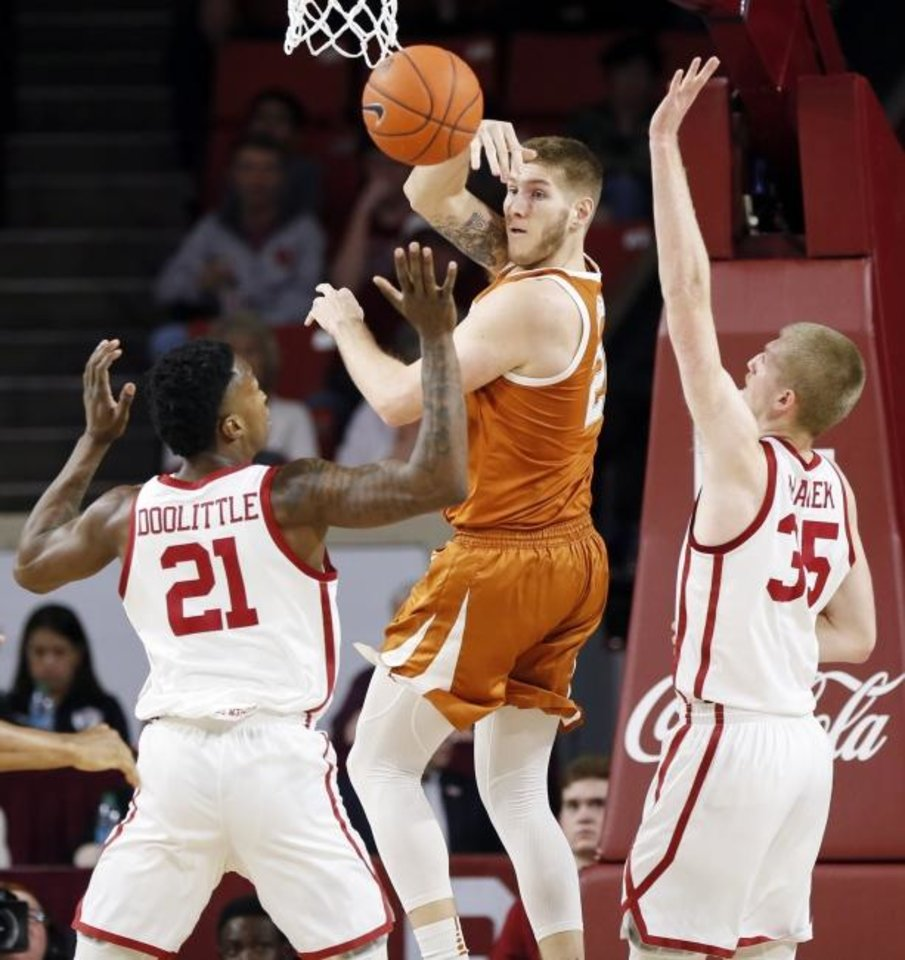 Photo -  Texas' Dylan Osetkowski (21) passes between OU's Kristian Doolittle (21) and Brady Manek (35) during a game Feb. 23, 2019, in Norman. [Nate Billings, The Oklahoman]