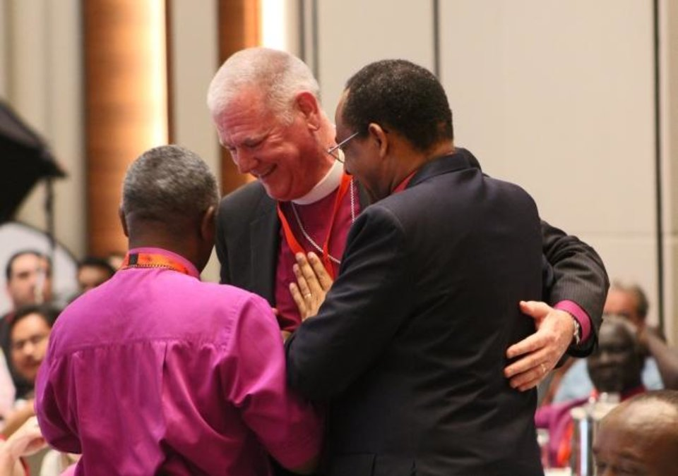 Photo -  Oklahoma Bishop Ed Konieczny, center, is embraced by Burundian Bishop Eraste Bigirimana, right, and Diocese of Nairobi Bishop Joel Waweru, both of whom opposed a resolution that Konieczny  proposed but they worked with him to craft a compromise at an Anglican Communion gathering in Hong Kong. [Paul Feheley/Anglican Communion News Service]