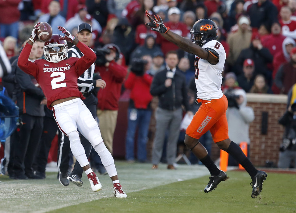 Photo - Oklahoma's CeeDee Lamb (2) makes a catch in the third quarter as Oklahoma State's Rodarius Williams (8) defends during a Bedlam college football game between the University of Oklahoma Sooners (OU) and the Oklahoma State University Cowboys (OSU) at Gaylord Family-Oklahoma Memorial Stadium in Norman, Okla., Nov. 10, 2018.  OU won 48-47. Photo by Sarah Phipps, The Oklahoman