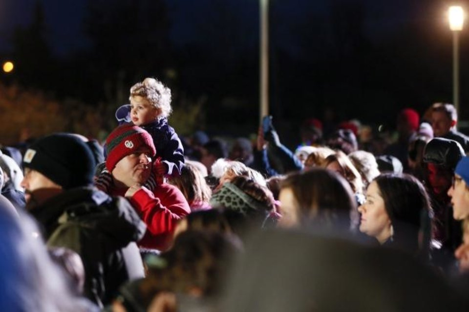 Photo -  A child sits on a man's shoulders in the crowd braving the cold weather during the Governor's Christmas Tree Lighting at the Oklahoma History Center in Oklahoma City, Monday, Dec. 9, 2019. [Nate Billings/The Oklahoman]