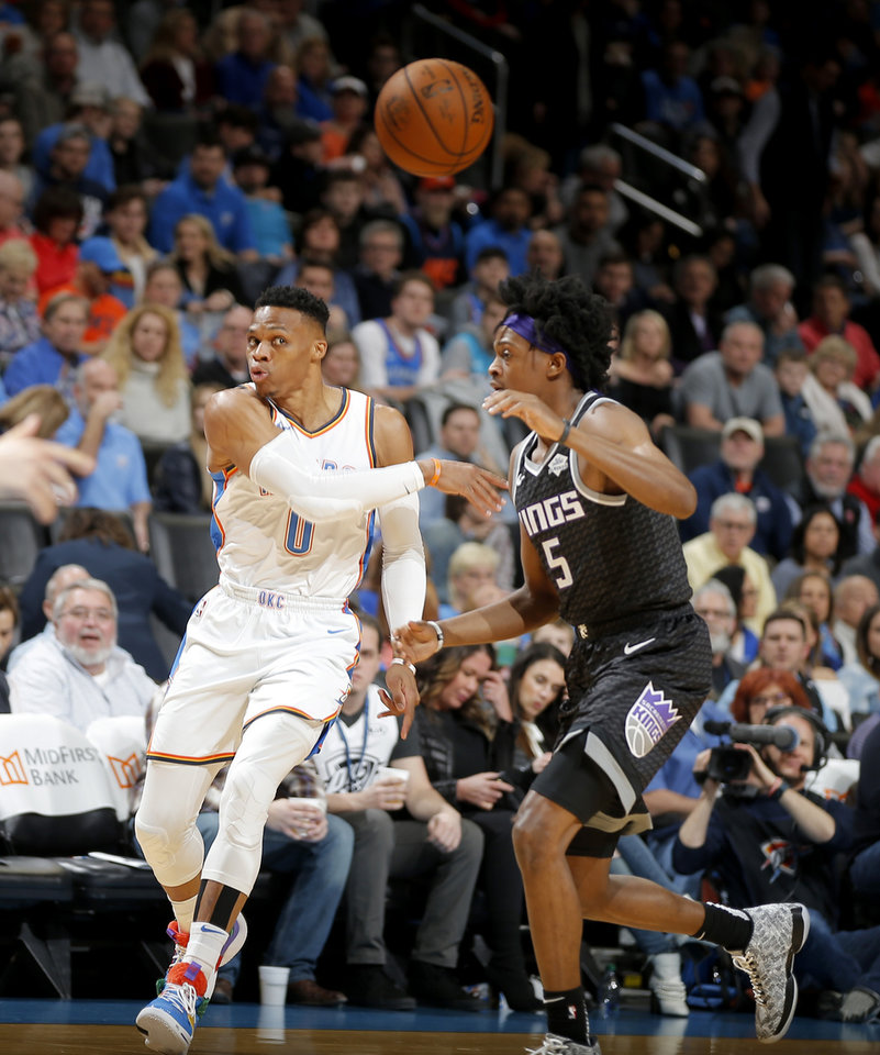 Photo - Oklahoma City's Russell Westbrook (0) passes over /Sacramento's De'Aaron Fox (5) during an NBA basketball game between the Oklahoma City Thunder and the Sacramento Kings at Chesapeake Energy Arena in Oklahoma City, Saturday, Feb. 23, 2019. Photo by Bryan Terry, The Oklahoman