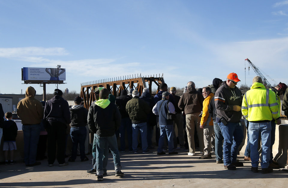 Photo -  People watch workers install the new railroad bridge over Interstate 235 in Oklahoma City. [Photo by Sarah Phipps, The Oklahoman]